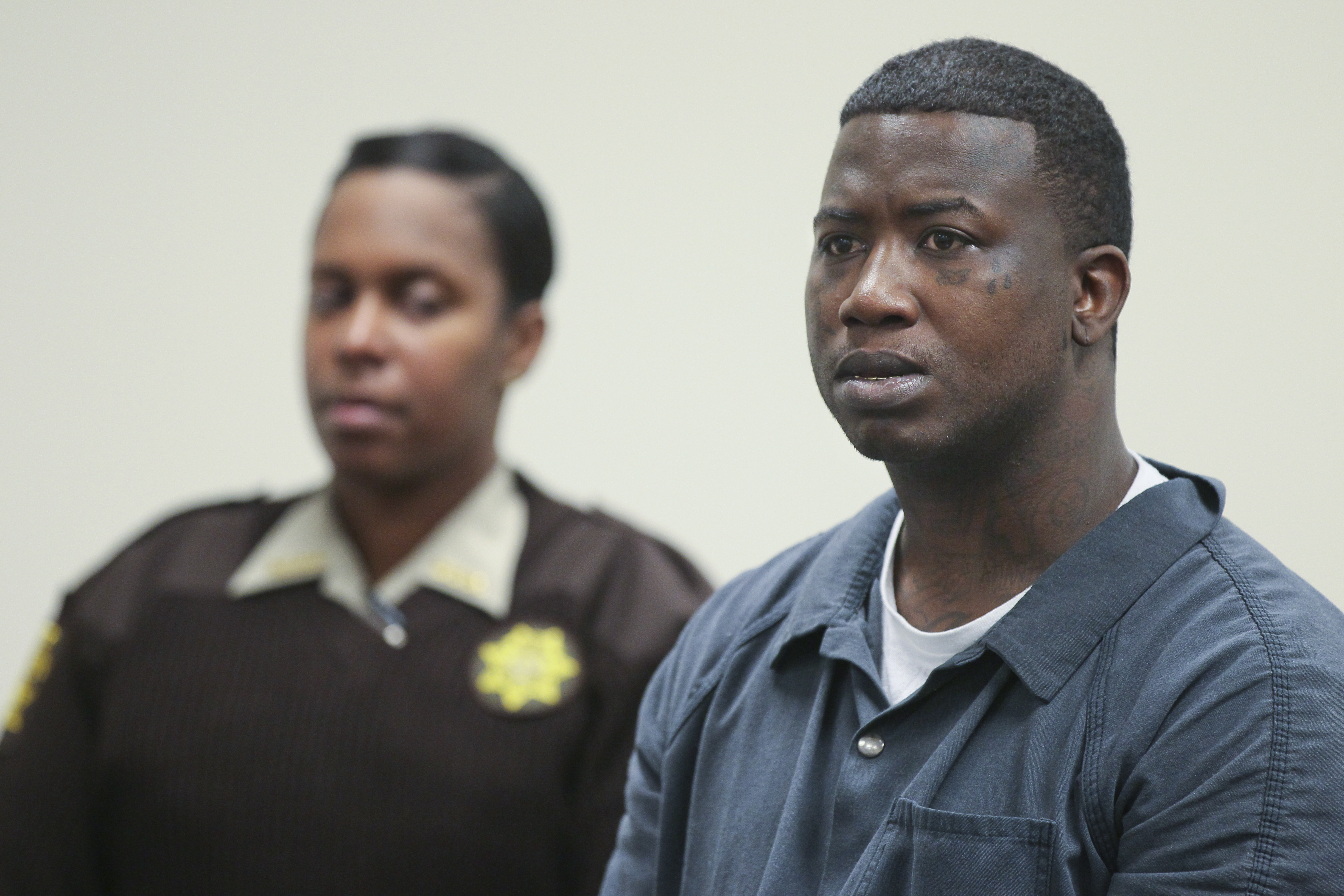 """Mar. 27, 2013 Atlanta: Fulton County Sheriff deputy T. Reynolds (left) looks on as defendant Radric Davis (right) listens. Rapper Gucci Mane was denied bond Wednesday at his first court appearance after his arrest for allegedly assaulting a soldier earlier this month at an Atlanta nightclub. His next court date is April 10. The musician, whose real name is Radric Davis, was booked into the Fulton County Jail Tuesday, charged with aggravated assault with a weapon, according to online jail records. Fulton County sheriff's spokeswoman Tracy Flanagan said Davis turned himself in at the jail about 11:30 p.m. Tuesday, and will face a magistrate for a first appearance at 11 a.m. Wednesday. Channel 2 Action News reported last week that Atlanta police had issued a warrant for the rapper following the March 16 incident at the Harlem Nights club on Courtland Street. The alleged victim told Channel 2 that Davis hit him in the head with a champagne bottle after he asked to take a photo with the rapper. """"I'm in the military. I wanted to get a picture with Gucci Mane, is it okay?"""" the soldier said he asked a security guard. """"I was speaking to the security guard, and Gucci Mane hit me in the head with a bottle,"""" the solder told Channel 2. The soldier told the station that he went to Grady Memorial Hospital by ambulance, and his injury required 10 stitches. JOHN SPINK / JSPINK@AJC.COM"""